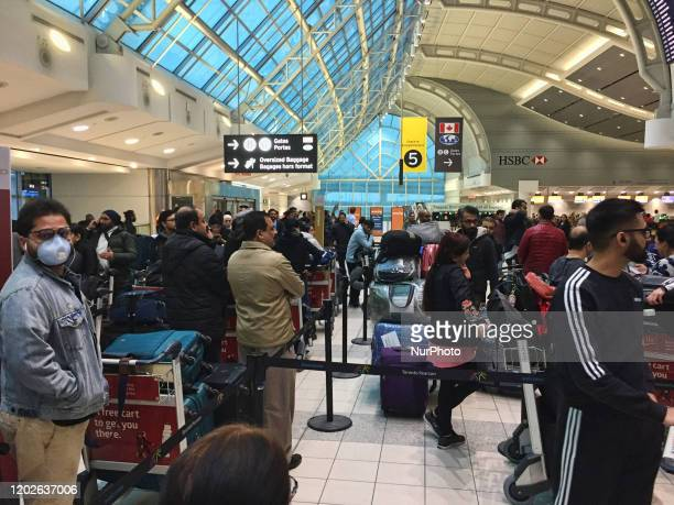 Crowd of passengers waiting to check-in for their flight at Pearson International Airport in Ontario, Canada. Some passangers are wearing masks to...