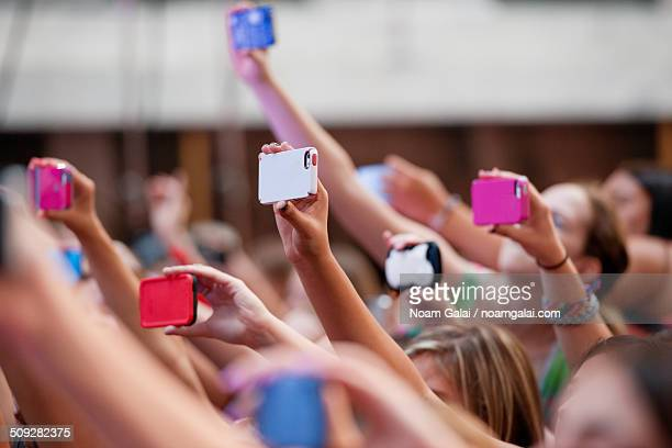 Crowd of people at a concert using mobile phones
