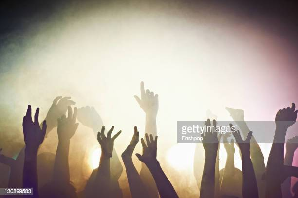 crowd of people at concert waving arms in the air - arme hoch stock-fotos und bilder