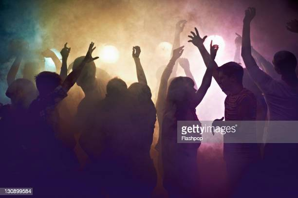 crowd of people at concert waving arms in the air - dancing stockfoto's en -beelden
