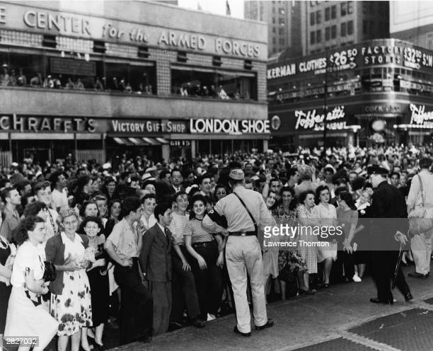 A crowd of people at the corner of 42nd Street and Broadway celebrate the end of World War II on VJ Day in New York City August 14 1945