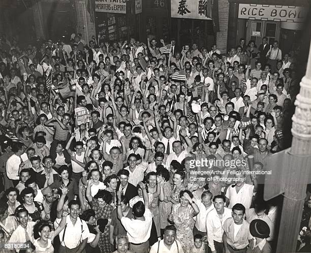 A crowd of people celebrate the end of World War II VJ Day in Chinatown a few people hold American flags a person holds up a New York Post newspaper...