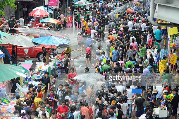 CONTENT] Crowd of people celebrating Songkran on a street in Si Lom Bang Rak district Bangkok Jets of water are being sprayed from a number of hoses...