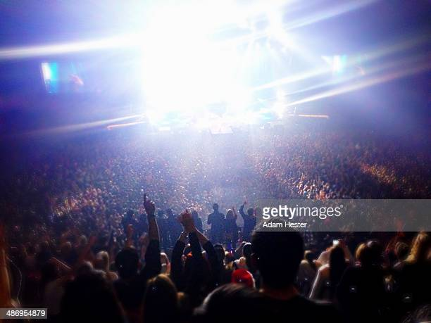 A crowd of people cheer and applaud for a band inside of the Bill Graham Civic Center in San Francisco California