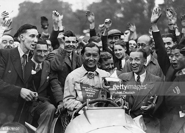 A crowd of people congratulate Prince Bira of Spain after he won an International Car Race