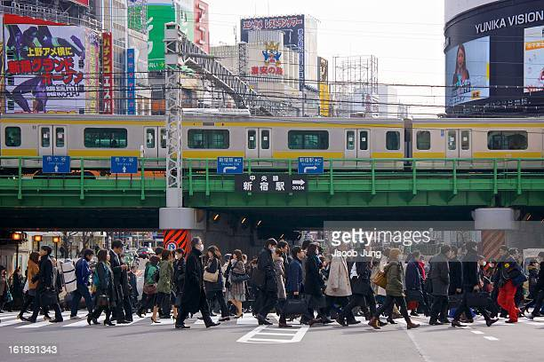 CONTENT] Crowd of people crosses the street in in Tokyo's busy Shinjuku Ward Behind the crowd a JR train travels along an overpass and buildings...