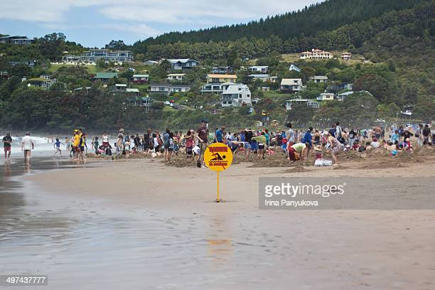 CONTENT] A crowd of people digging their own personal own spa pools using hot spring water from under the sand at Hot Water Beach in The Coromandel...