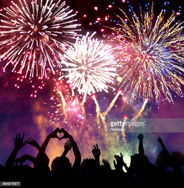 crowd of people enjoying firework display - fireworks stock pictures, royalty-free photos & images