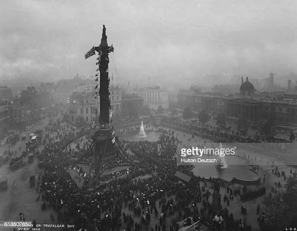 A crowd of people gathers in Trafalgar Square to celebrate Trafalgar Day