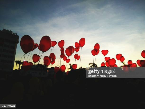 Crowd Of People Holding Heart Shape Balloons