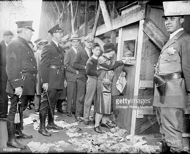 Crowd of people including police officers standing in front of a wooden booth in front of Wrigley Field located at 1060 West Addison Street during...