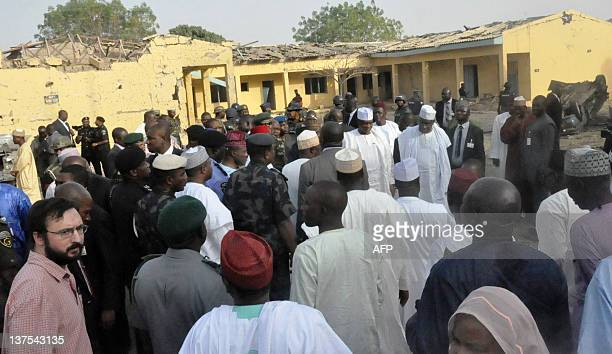 A crowd of people is gathered as Nigerian President Goodluck Jonathan visits the burnt office of the Assitant Inspector General of police in charge...