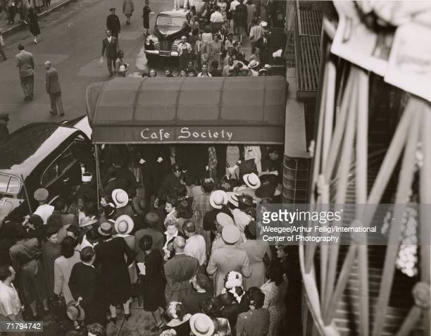 A crowd of people is held back on the sidewalk under an awning in front of the Cafe Society Uptown nightclub by policemen during the wedding...
