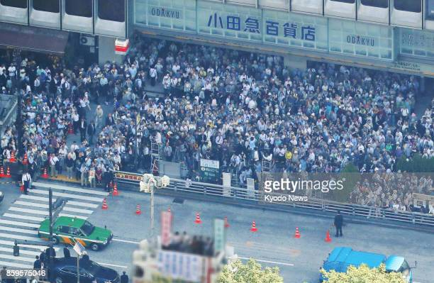 A crowd of people listen to a stump speech given by a candidate in front of a department store in Tokyo's Shinjuku Ward in this photo taken from a...