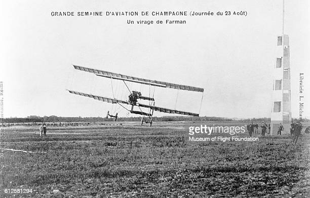 A crowd of people look on as a Farman III sport/exhibition airplane takes flight at the Rheims Airshow in the Champagne district of France in August...