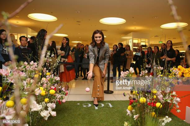 A crowd of people look on as Sarah Ellen plays a bowling game inside David Jones during Vogue American Express Fashion's Night Out 2017 on September...