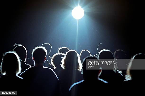 Crowd of people looking at bright light, rear view
