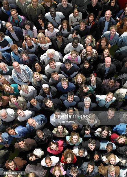 Crowd of people looking upwards, smiling, overhead view