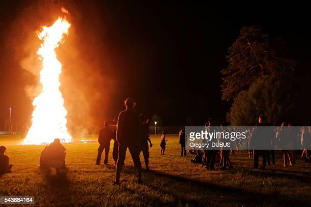 Crowd of people meeting around big bonfire in summer