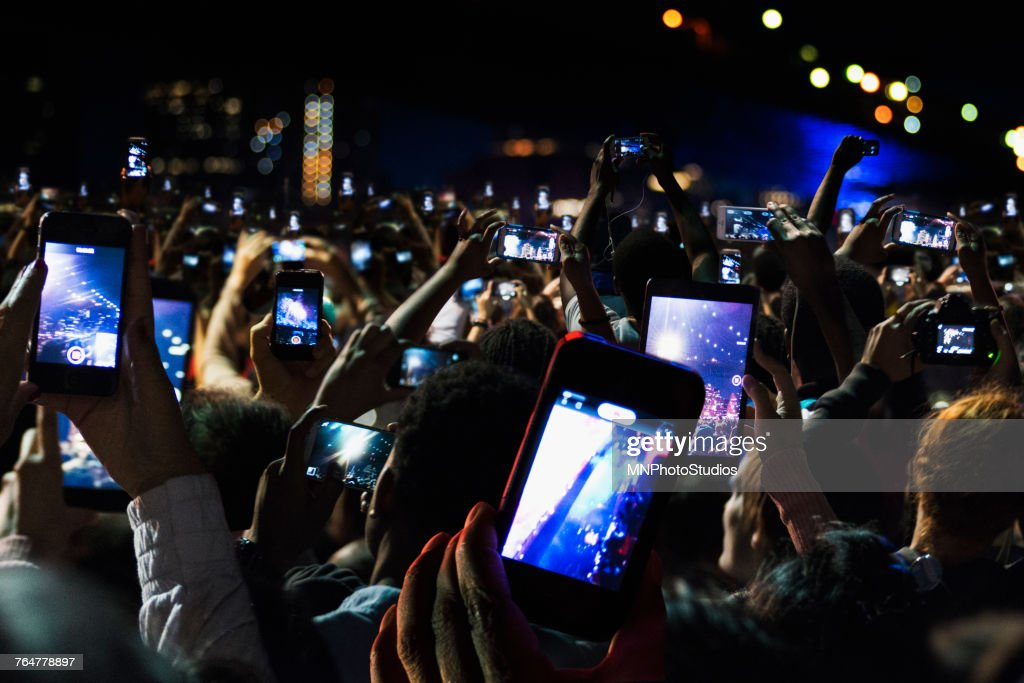 Crowd of people recording video with cell phones at night : Foto de stock