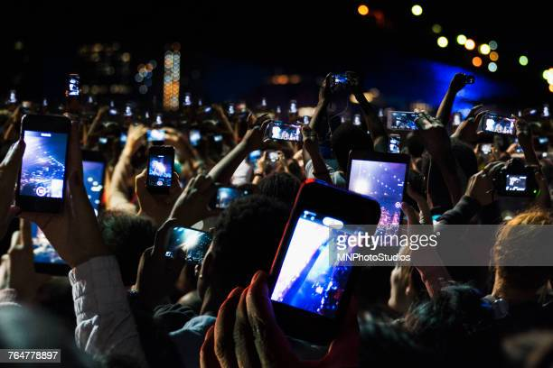 crowd of people recording video with cell phones at night - concert photos et images de collection