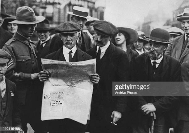A crowd of people sharing a newspaper after the announcement of the signing of the Armistice which ended World War I November 1918