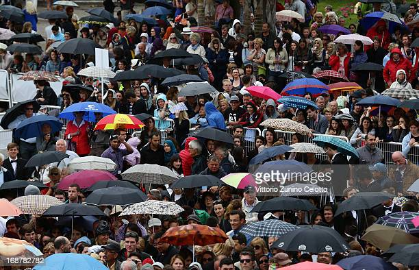 A crowd of people shelter under umbrellas as they wait for the Opening Ceremony and 'The Great Gatsby' Premiere during the 66th Annual Cannes Film...