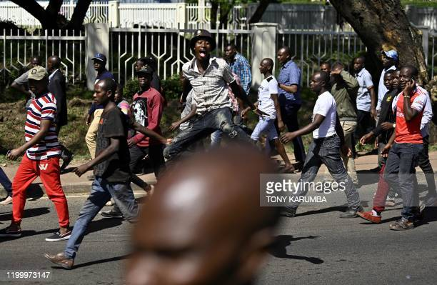 A crowd of people shuffle hurriedly towards the Nyayo National Stadium where the flagdraped casket bearing the body of Kenya's former president...
