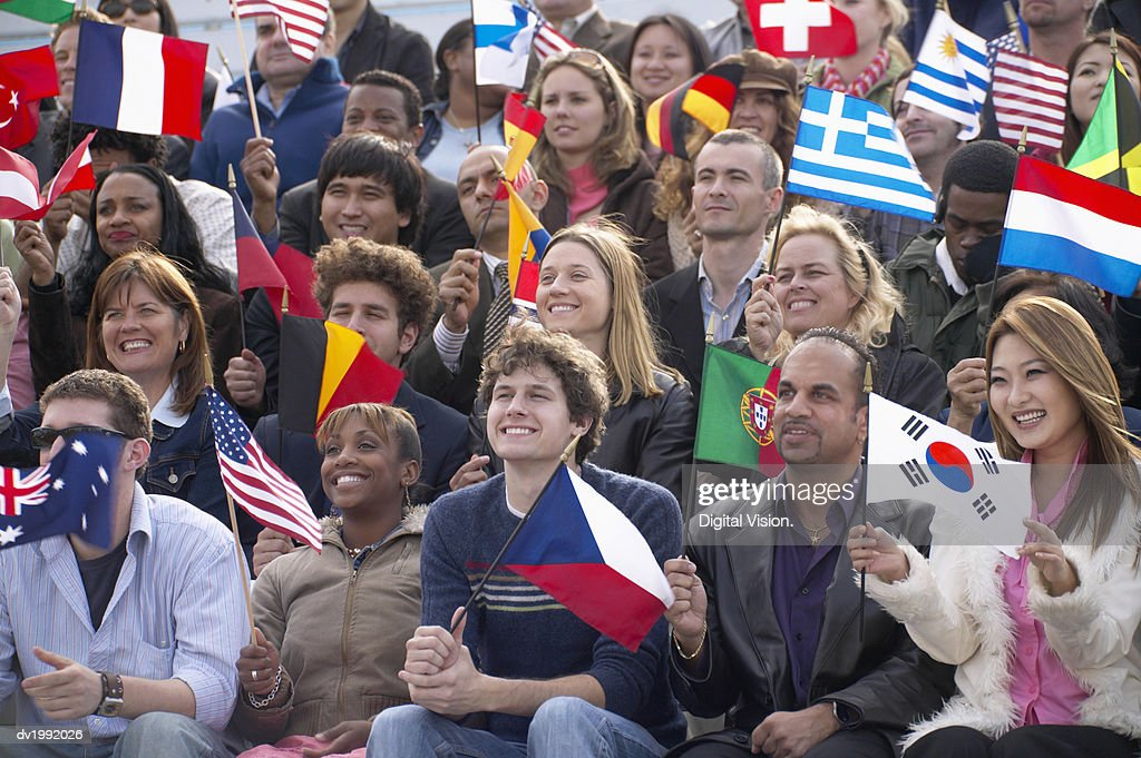 Crowd of People Sitting Holding Flags : Stock Photo