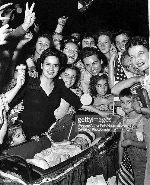 Crowd of people some holding American flags and noise makers with little Bobby De Marco a baby aged 7 months in a carriage celebrating the end of...