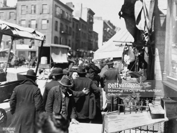 Crowd of people stand on the sidewalks, shopping from stands as horsedrawn carriages travel behind them, on Mulberry Street, New York City.