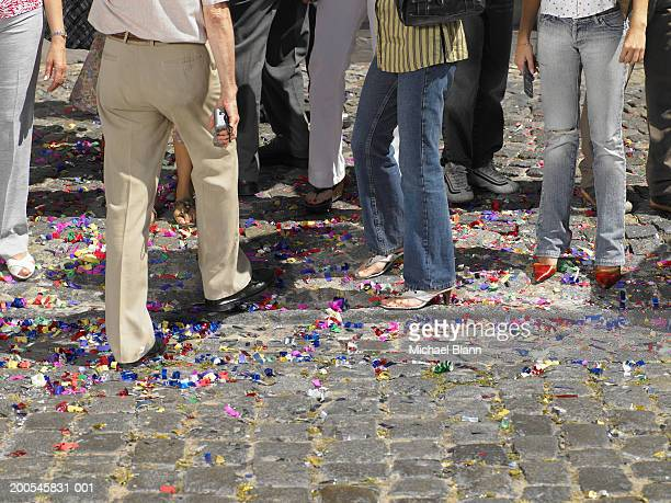 crowd of people standing on coloured confetti in street, low section - low section stock pictures, royalty-free photos & images
