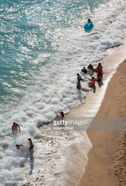 crowd of people swimming on the beach in kaputaş, antalya, turkey - kas stock pictures, royalty-free photos & images
