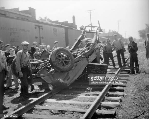A crowd of people views the remains of a Keystone Fuel Material Co truck after it was crushed by a Milwaukee Road train near the Brittingham Park...