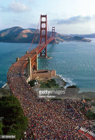 a crowd of people walk across the golden gate bridge for