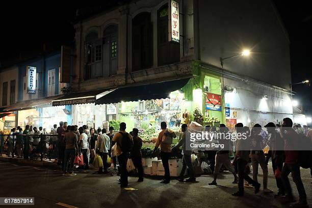 crowd of people walking a row of shop houses. - caroline pang stock pictures, royalty-free photos & images
