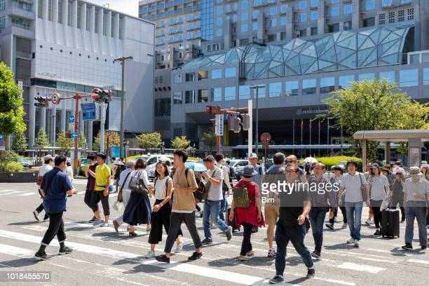 crowd of people walking across road in kyoto, japan - pedestrian crossing sign stock photos and pictures