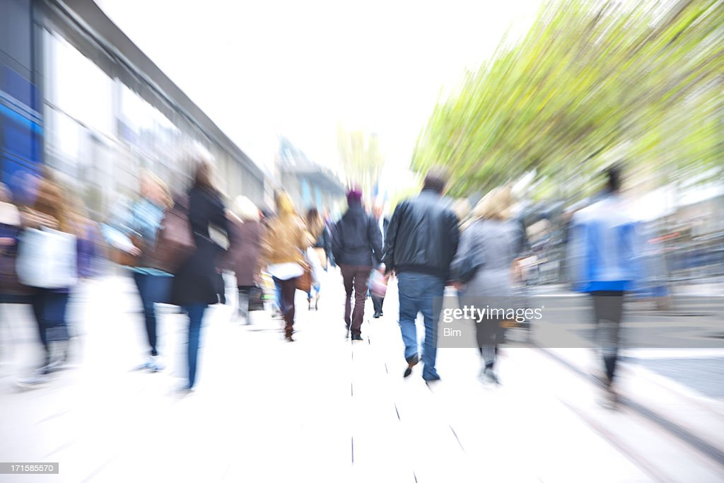 Crowd of People Walking Down Walkway Past Stores, Blurred Motion : Stock Photo