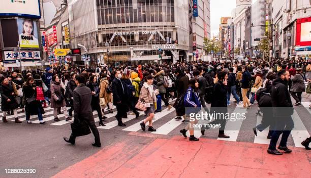 Crowd of people walking in various directions crossing the Shibuya crossing in Tokyo in Japan.