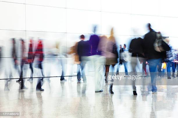 crowd of people walking indoors down walkway, blurred motion - motion blur stock photos and pictures