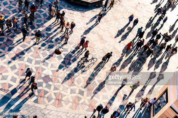 crowd of people walking on a city square at sunset - drone point of view stock pictures, royalty-free photos & images