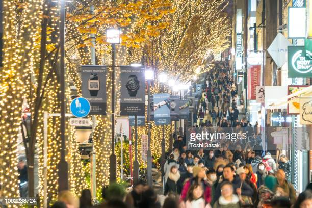 a crowd of people walks down the sidewalk beside the omotesando street among the illuminated row of zelkova trees and many fashion boutiques for winter holydays season in the night at jingumae, shibuyatokyo japan on december 06 2017. - 表参道 ストックフォトと画像
