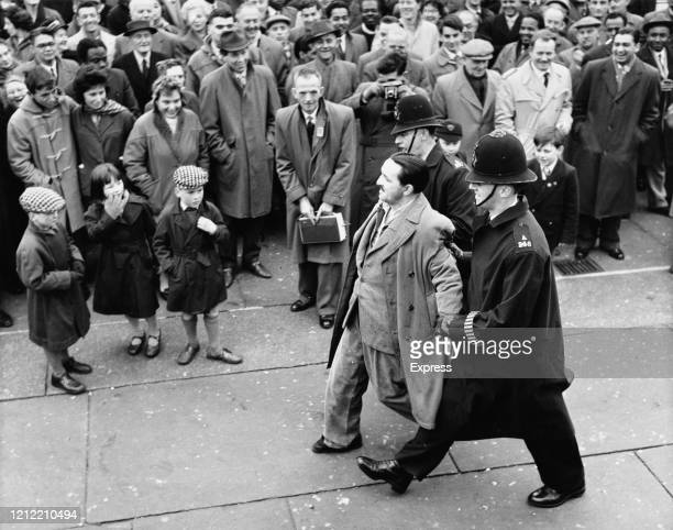Crowd of people watch a protestor being carried away at an Anti-apartheid protest in London, Uk, 28th March 1960.