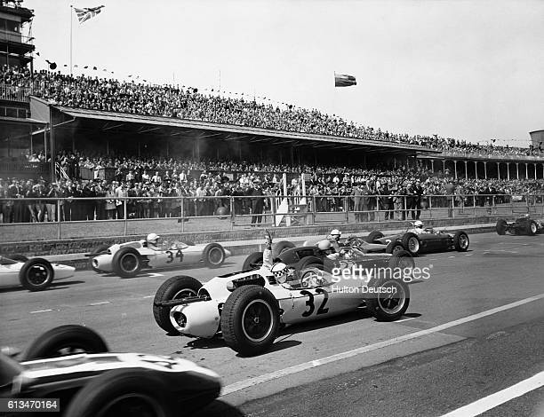 A crowd of people watch the racecars waiting on the starting grid for the beginning of the British Grand Prix