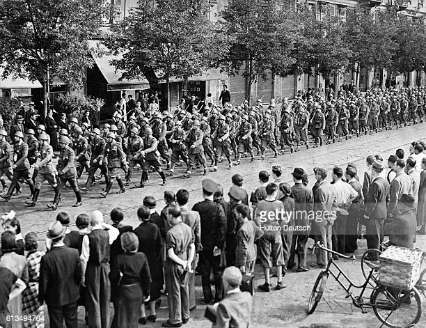 A crowd of people watch the the legionnaires marching to the station for the start of a journey to East Africa