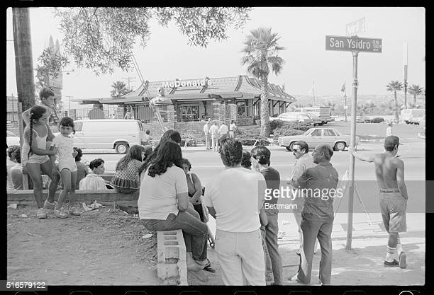 A crowd of people watches the scene outside the McDonald's restaurant in which a lone gunman killed 20 people in San Ysidro California