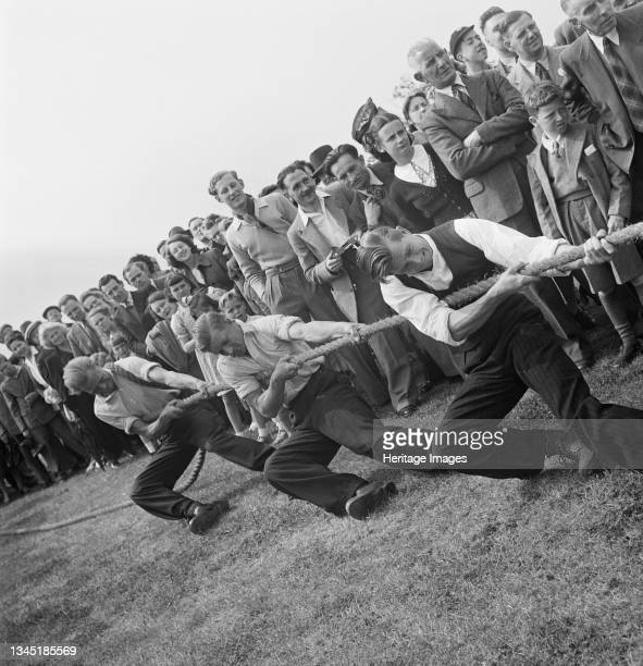 Crowd of people watching a tug of war match during the opening of a new sports ground at Elstree. This photograph was taken at Elstree during the...