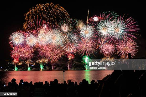 crowd of people watching colourful fireworks exploding over city buildings - australia day stock pictures, royalty-free photos & images