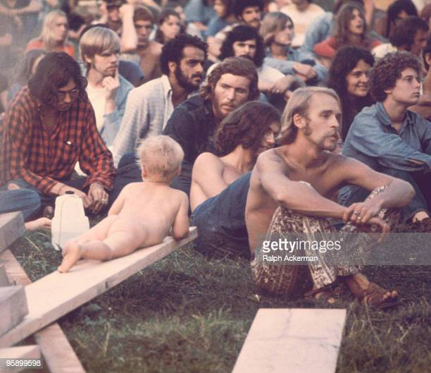 A crowd of people watching Hog Farmers' free stage show at the Woodstock Music Festival Bethel NY 1969