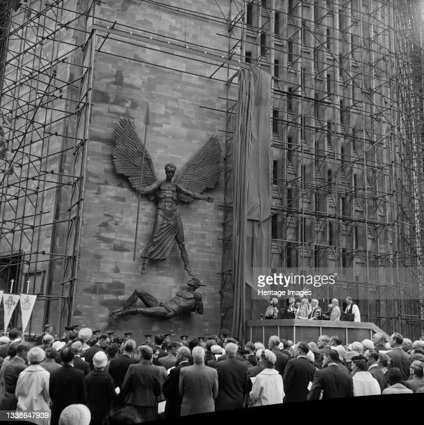 Crowd of people watching the unveiling ceremony of the statue St Michael and the Devil by sculptor Sir Jacob Epstein at Coventry Cathedral. The...